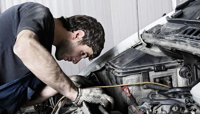 hombre arreglando carro